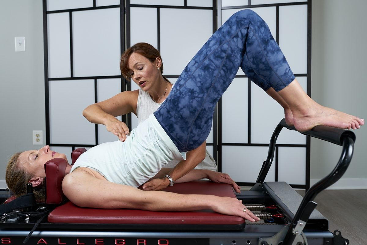 Mariah cueing a client on the Reformer during comprehensive teacher training program