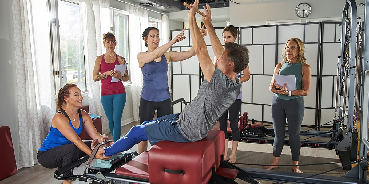 Pilates students reviewing an exercise during comprehensive pilates teacher training program