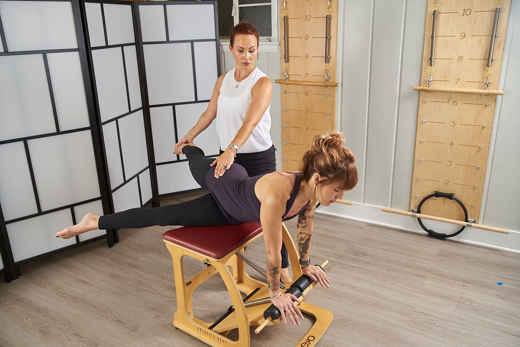 Instructor teaching a client how to perform Swan on Pilates Chair
